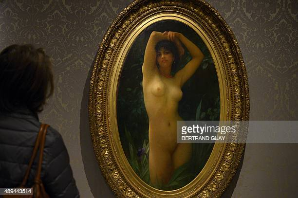 A visitor looks at a painting entitled 'La fille aux joncs ou la baigneuse' by Ernest Hebert during the exhibition Splendour and Misery Pictures of...