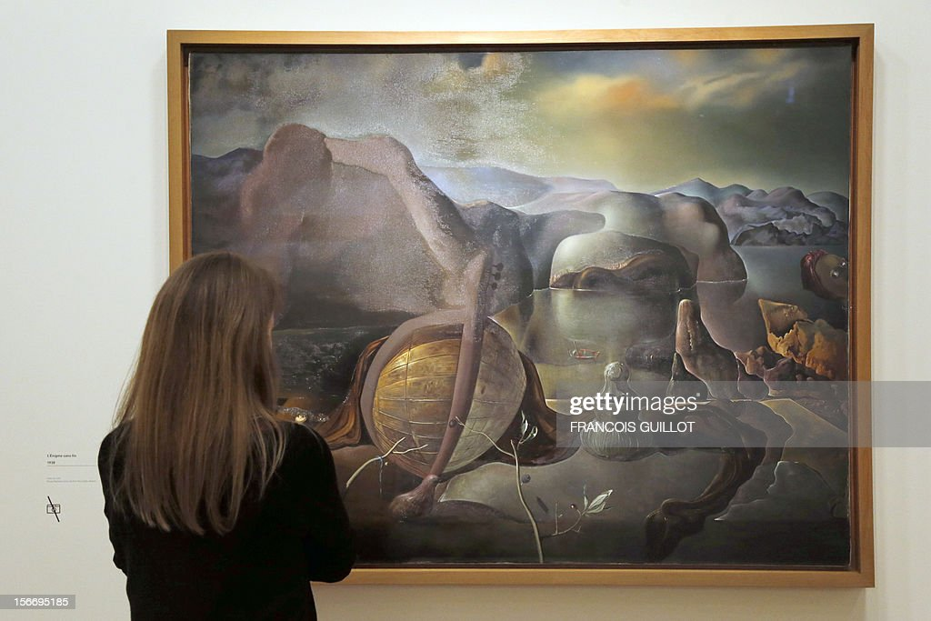 A visitor looks at a painting entitled 'L'enigme sans fin' (Endless enigma) by Spanish surrealist artist Salvador Dali during an exhibition devoted to his work at the Centre Pompidou contemporary art center (aka Beaubourg) on November 19, 2012 in Paris. More than 30 years after the first retrospective in 1979, the event gathers more than 200 art pieces and runs until March 13, 2013. AFP PHOTO FRANCOIS GUILLOT