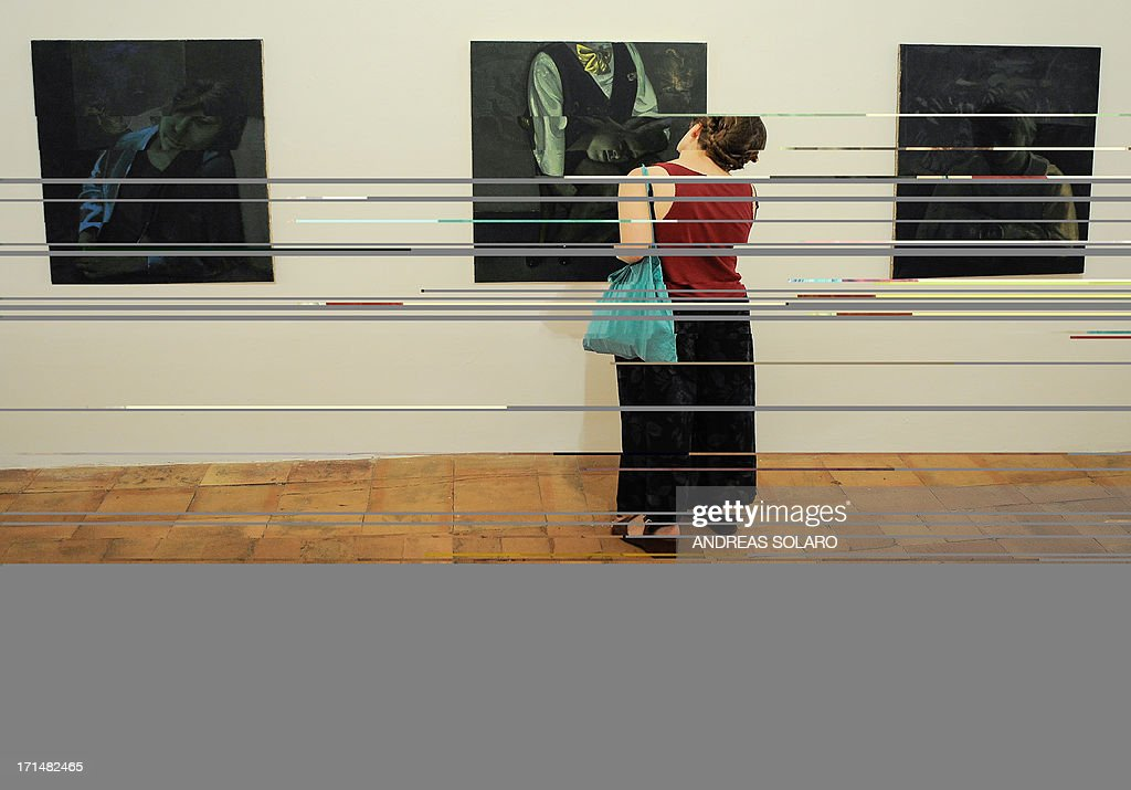 A visitor looks at a painting entitled 'Orlando' (C) by Romanian artist Victor Man on June 25, 2013 during an exhibition at the Villa Medici, the headquarters of the French Academy in Rome. AFP PHOTO / ANDREAS SOLARO CAPTION
