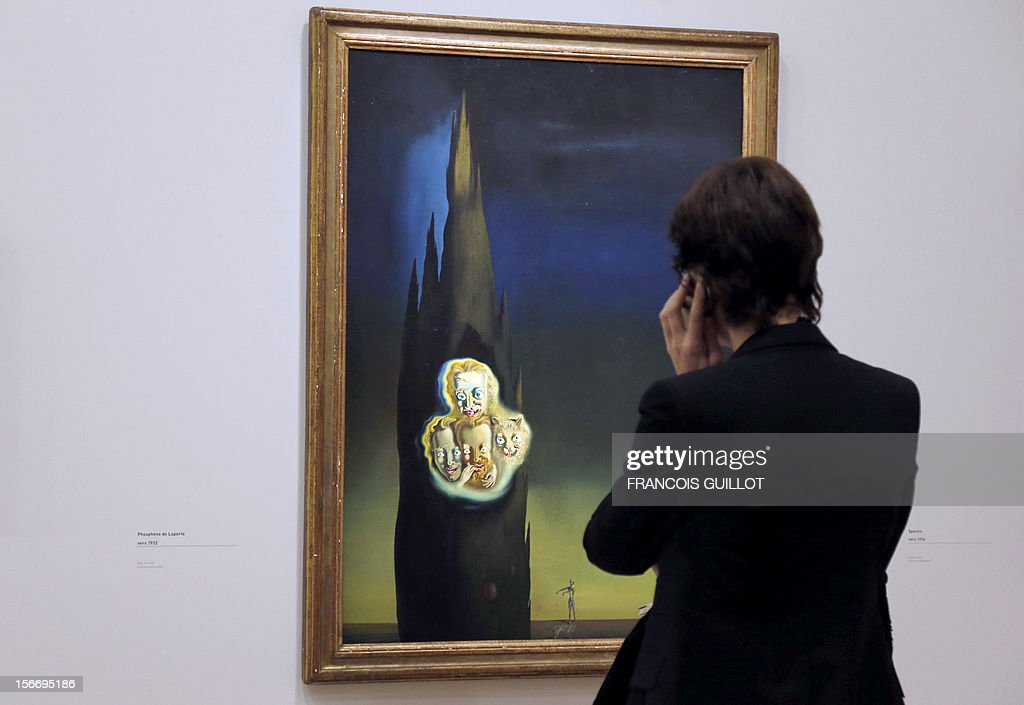 A visitor looks at a painting entitled 'Phosphene de Laporte' by Spanish surrealist artist Salvador Dali during an exhibition devoted to his work at the Centre Pompidou contemporary art center (aka Beaubourg) on November 19, 2012 in Paris. More than 30 years after the first retrospective in 1979, the event gathers more than 200 art pieces and runs until March 13, 2013.