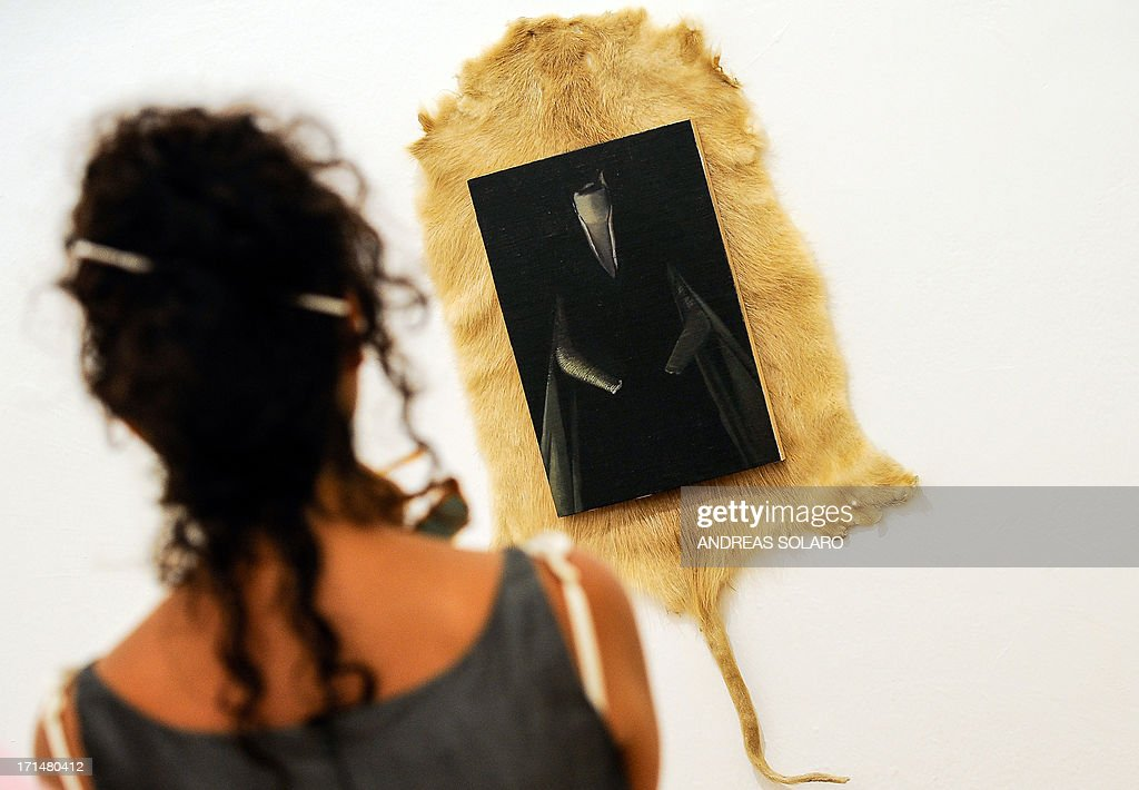 A visitor looks at a painting entitled 'Ubiquitous' by Romanian artist Victor Man on June 25, 2013 during an exhibition at the Villa Medici, the headquarters of the French Academy in Rome.