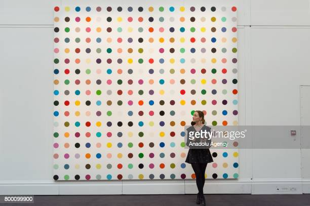 A visitor looks at a painting is titled 1Heptene by by artist Damien Hirst with an estimate of £500000£700000 in London United Kingdom on June 23...