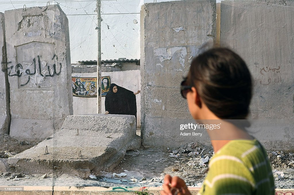 A visitor looks at a photo of a separation wall in Sadr City, Baghdad, Iraq as it hangs as part of the 'Wall on Wall' exhibition at the East Side Gallery section of the former Berlin Wall on July 10, 2013 in Berlin, Germany. A series of photos shot since 2006 by photographer Kai Wiedenhoefer hanging on the Western, river Spree side of the Wall features large pictures of separation barriers in Baghdad, Korea, Cyprus, Mexico, Morocco, Israel, Belfast, and in the former East Germany itself. The opposite side of the stretch of the original Wall is known as East Side Gallery, a memorial to peace and freedom covered in murals questioning the legacy of the original Wall, and the subject of several demonstrations earlier in March this year when a section of it were threatened with removal to make way for a construction site for luxury apartment buildings, discussion of which is still ongoing with a decision expected to be reached in early August.
