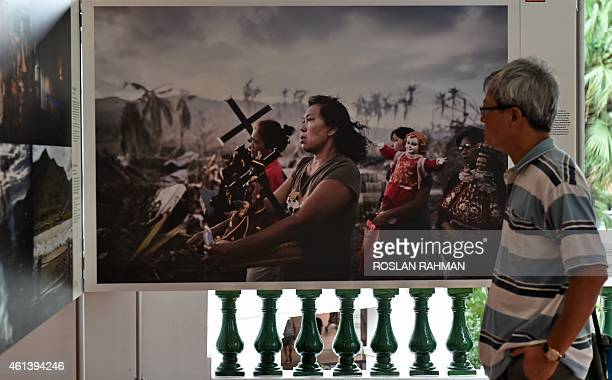 A visitor looks at a photo taken by AFP photographer Philippe Lopez showing survivors of Super Typhoon Haiyan in the Philippines displayed among...