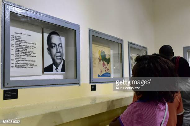 A visitor looks at a photograph as she visits the Civilisation Museum of Abidjan on September 29 2017 during the first exhibition called...