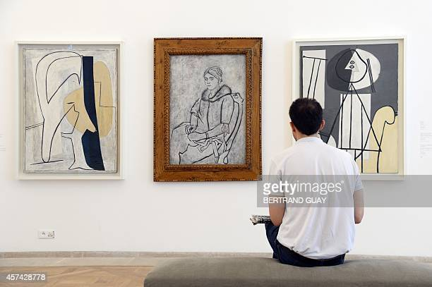 A visitor looks at a Picasso paintings 'Figure 1927 ' 'Olga in a fur collar 1923 ' and ' Painter with palette and easel 1928 ' during the press day...