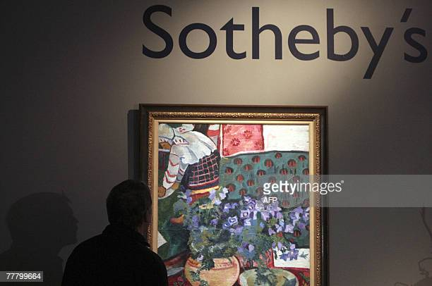 A visitor looks at a picture Bluebells by Russian artist Natalia Goncharova during an exhibition of Sotheby's the world's oldest international...