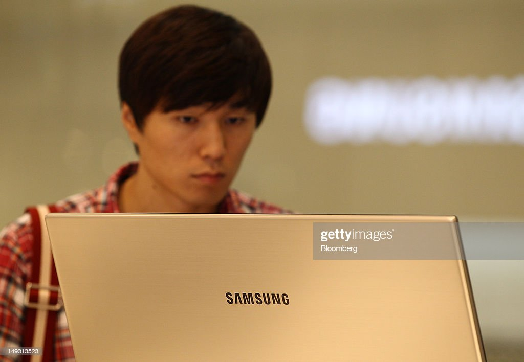 A visitor looks at a Samsung Electronics Co. monitor at the company's flagship store in Seoul, South Korea, on Thursday, July 26, 2012. Samsung, the world's largest maker of TVs and mobile phones, reported second-quarter profit that missed analysts' estimates after chip prices weakened and smartphone output failed to keep up with demand. Photographer: SeongJoon Cho/Bloomberg via Getty Images