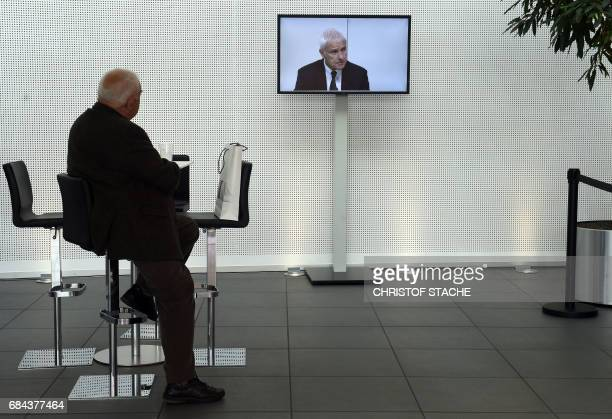 A visitor looks at a screen displaying Matthias Mueller chairman of the supervisory board of German car maker Audi and CEO of German car maker...