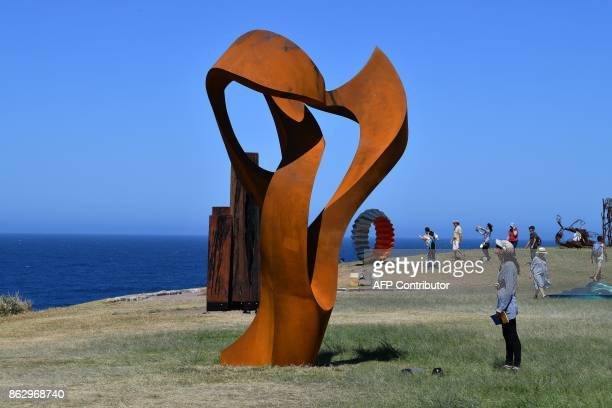A visitor looks at a sculpture by artist Johannes Pannekoek as part of the 'Sculpture by the Sea' exhibition near Bondi beach in Sydney on October 19...