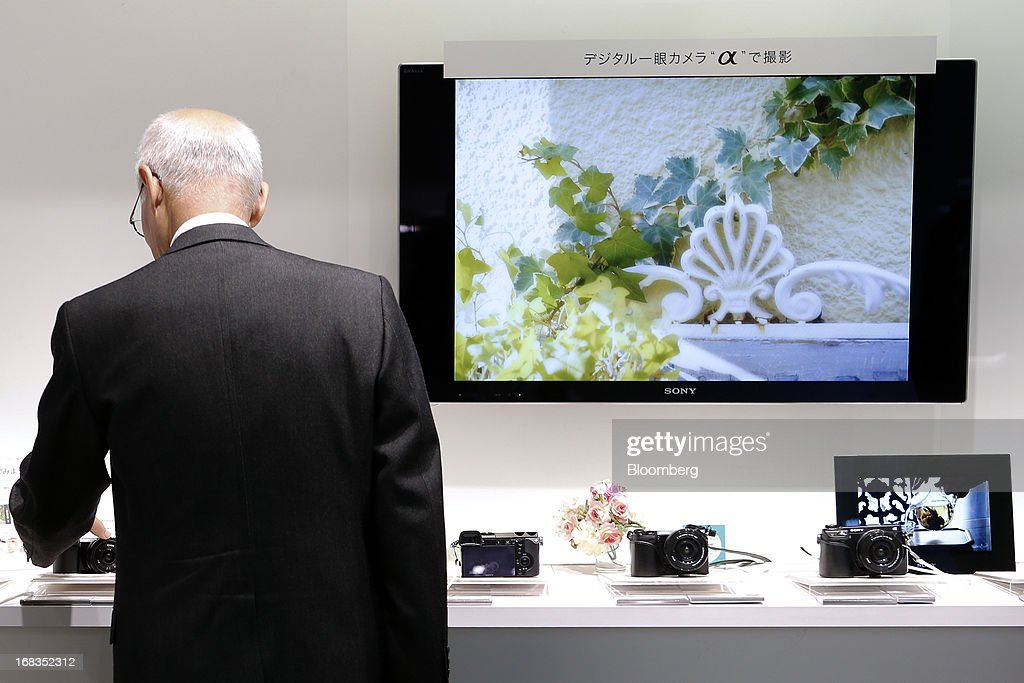 A visitor looks at a Sony Corp. NEX interchangeable lens camera displayed at the company's showroom in Tokyo, Japan, on Thursday, May 9, 2013. Sony forecast a smaller-than-expected annual profit as its Xperia smartphones and Bravia TVs struggle to regain market share from Apple Inc. and Samsung Electronics Co. Photographer: Kiyoshi Ota/Bloomberg via Getty Images
