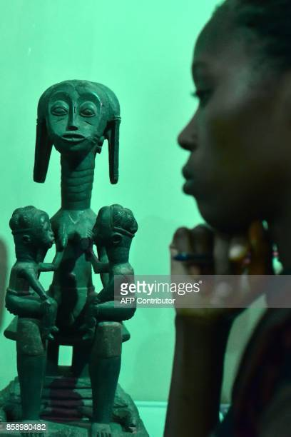 A visitor looks at a statue exhibited at the Civilisation Museum of Abidjan on September 29 2017 during the first exhibition called 'Renaissance'...