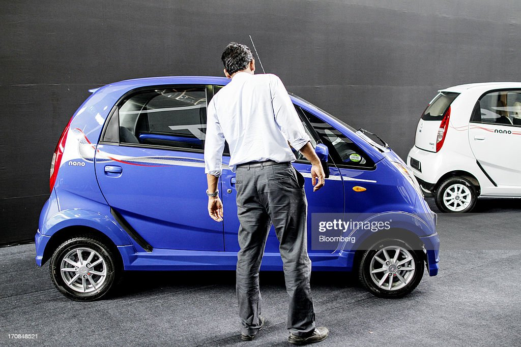 A visitor looks at a Tata Motors Ltd. Nano automobile on display during a Tata Motors media event in Pune, India, on Wednesday, June 19, 2013. Tata Motors announced the introduction of 8 new models today. Photographer: Dhiraj Singh/Bloomberg via Getty Images
