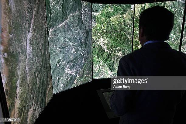A visitor looks at a threedimensional rendering of French mountains using Google Earth software on September 26 2012 at the official opening party of...