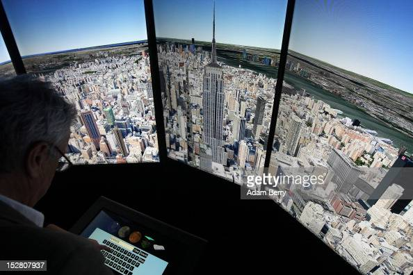 A visitor looks at a threedimensional rendering of Manhattan while using Google Earth software on September 26 2012 at the official opening party of...