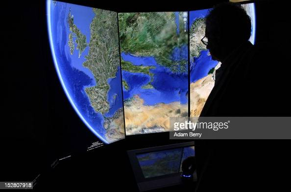 A visitor looks at a threedimensional rendering of the planet Earth while using Google Earth software on September 26 2012 at the official opening...
