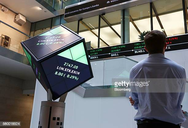 A visitor looks at a ticker of share prices as the London Stock Exchange share price sits displayed on an illuminated rotating cube in the atrium of...