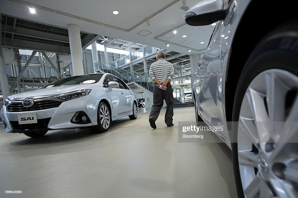 A visitor looks at a Toyota Motor Corp. Sai hybrid vehicle, left, displayed at the company's showroom in Tokyo, Japan, on Tuesday, Nov. 5, 2013. Toyota, the world's largest automaker, will probably deliver record semiannual profit when it reports earnings tomorrow, as the weaker yen bolsters the value of Japanese cars sold overseas. Photographer: Kiyoshi Ota/Bloomberg via Getty Images