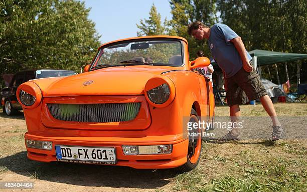 A visitor looks at a Trabant automobile at a Trabant enthusiasts' weekend on August 8 2015 near Nossen Germany The Trabant also called the Trabi is...