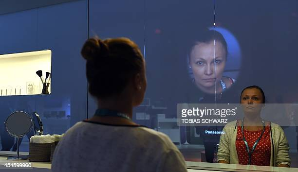 A visitor looks at a virtual makeup mirror at the booth of Panasonic during the second press day of the consumer electronics trade fair...