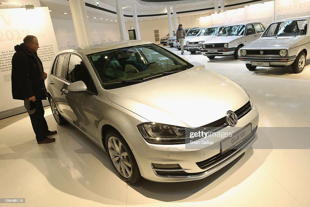 A visitor looks at a VW Golf VII as the six previous generations of Volkswagen cars stand lined up behind at a Volkswagen Group showroom on January 14, 2013 in Berlin, Germany. Volkswagen Group, which includes the VW, Audi, Porsche, Skoda, SEAT, Bentley and Bugatti brands, delivered a record 9.07 million cars to customers in 2012. Rising sales in the Americas and Asia helped to offset a drop in sales in western Europe.