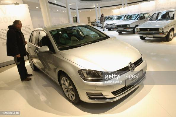 A visitor looks at a VW Golf VII as the six previous generations of Volkswagen cars stand lined up behind at a Volkswagen Group showroom on January...