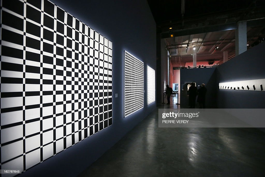 A visitor looks at a work of Argentinian artist Julio Le Parc, a pioneer of Op Art (Optical art), aged 85, at the Palais de Tokyo museum in Paris on February 25, 2013. The event will run from February 27 to May 13, 2013. LtoR, 'Progressive ambivalent sequences', 'Instability' and 'Rotation sequences' works.