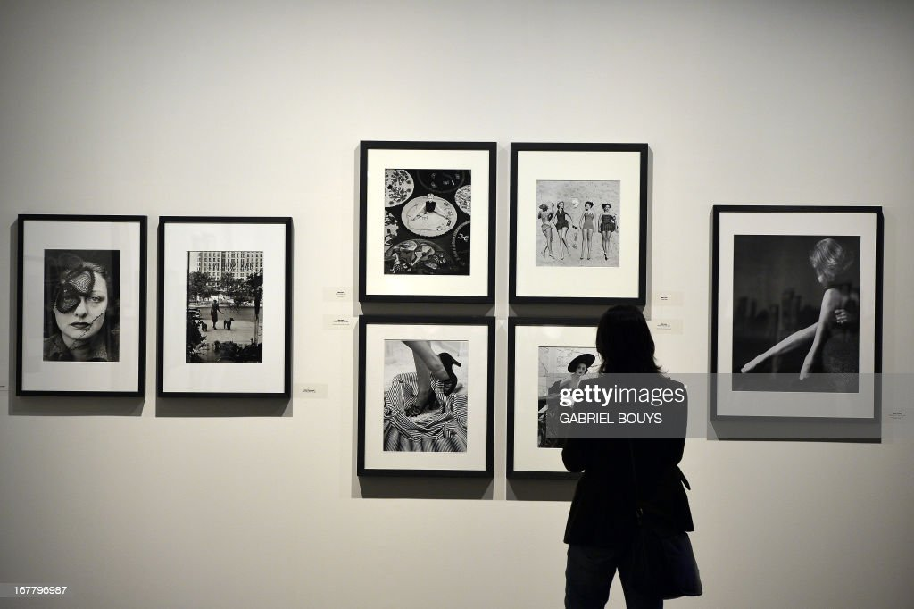 """A visitor looks at (L) Alfred Eisenstaedt's """"Model Janet MacLeod, New York, 1937"""" and Nina Leen 4 pictures (C) - Milton Green """"Marlene Dietrich, New York, 1952"""" (R) - during the 'Life. I grandi fotografi' (Life. The great photographers) exhibition at the auditorium on April 30, 2013 in Rome. The exhibition showing some 150 pictures taken from 1936 when the US magazine Life magazine premiered will be open from May, 1 to August 4, 2013."""