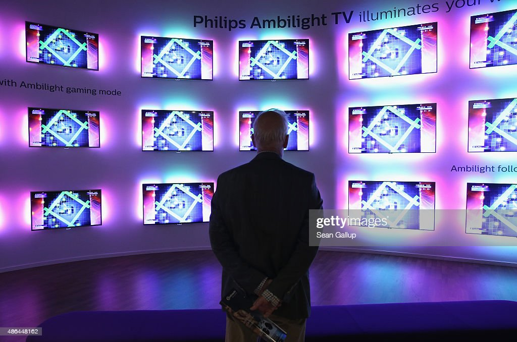 A visitor looks at Ambilight televisions at the Philips stand at the 2015 IFA consumer electronics and appliances trade fair on September 4, 2015 in Berlin, Germany. The 2015 IFA will be open to the public from September 4-9.