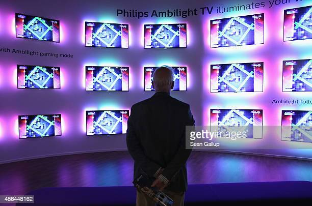 A visitor looks at Ambilight televisions at the Philips stand at the 2015 IFA consumer electronics and appliances trade fair on September 4 2015 in...