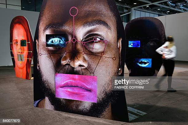A visitor looks at an art installation by US artist Tony Oursler entitled 'template/variant/friend/stranger' at Unlimited the Art Basel's pioneering...