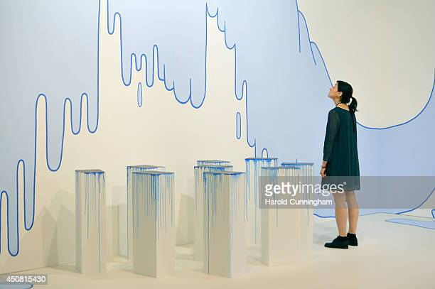 A visitor looks at an artwork by Lily van der Stokker and 'With every stencil a revolution one after another' by Latifa Echakhch in the gallery...
