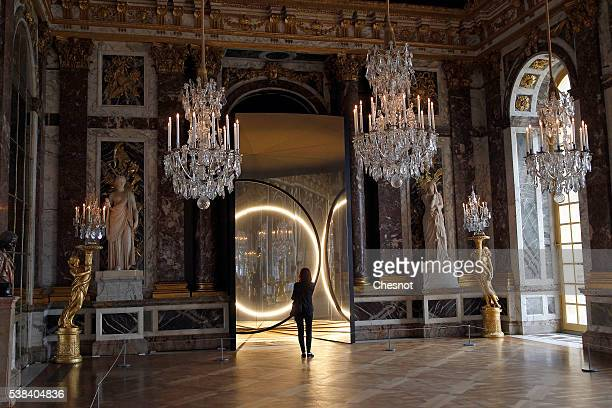A visitor looks at an artwork named 'Your sense of unity' by DanishIcelandic artist Olafur Eliasson displayed in the hall of mirrors of the Chateau...