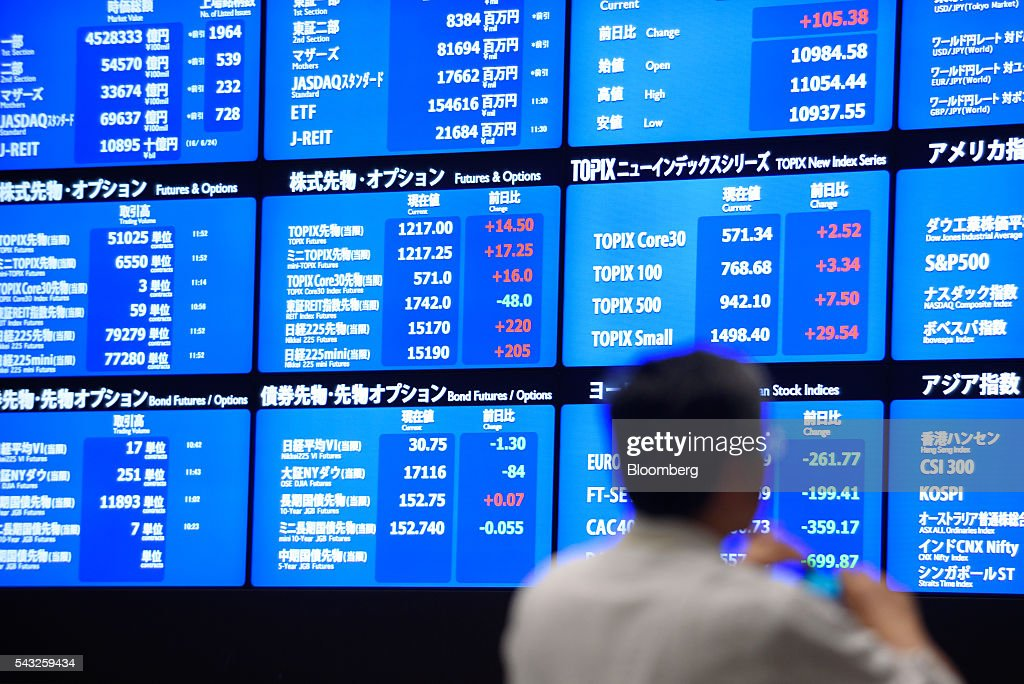 A visitor looks at an electronic board displaying market indices at the Tokyo Stock Exchange (TSE), operated by Japan Exchange Group Inc. (JPX), in Tokyo, Japan, on Monday, June 27, 2016. The yen was closing in on 99 per dollar at one point Friday and headed for its biggest gain since it was freely floated in February 1973, as Britain's vote to leave the European Union prompted investors to flee global markets and seek safety in Japanese government bonds. Photographer: Akio Kon/Bloomberg via Getty Images
