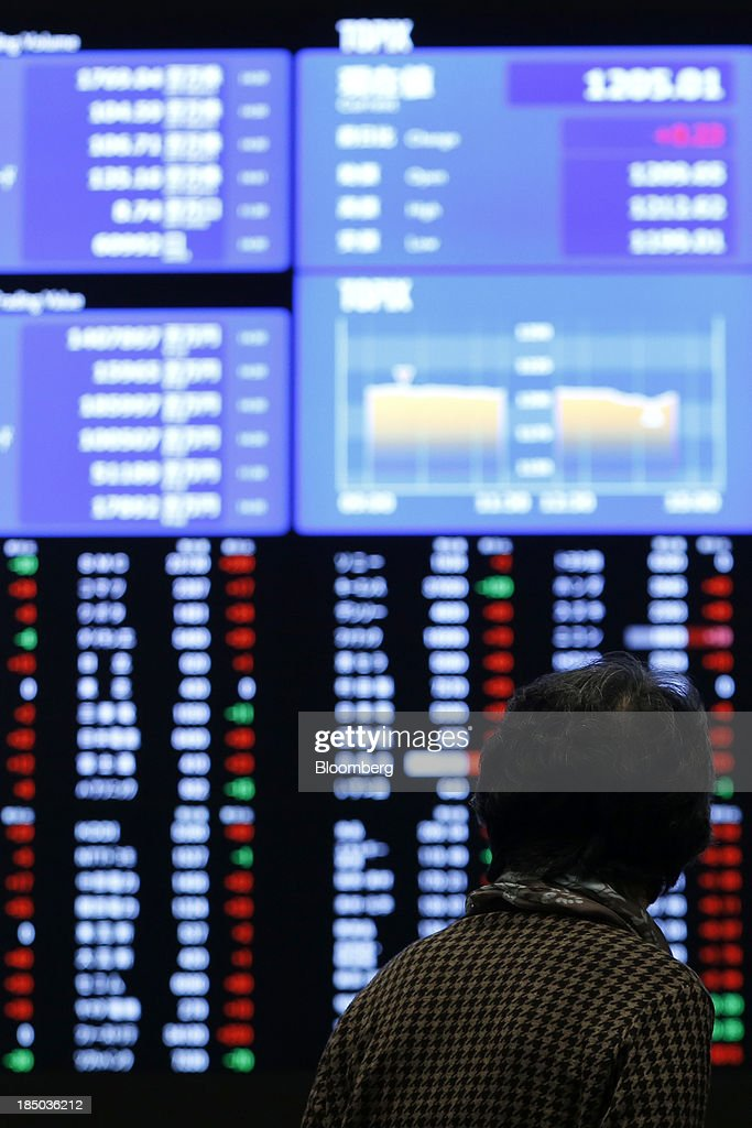 A visitor looks at an electronic board displaying stock figures at the Tokyo Stock Exchange (TSE) in Tokyo, Japan, on Thursday, Oct. 17, 2013. Japanese shares rose, with the Topix index climbing to a three-week high, after the U.S. Congress voted to end the government shutdown and raise the debt ceiling, ending the nation's fiscal impasse. Photographer: Kiyoshi Ota/Bloomberg via Getty Images