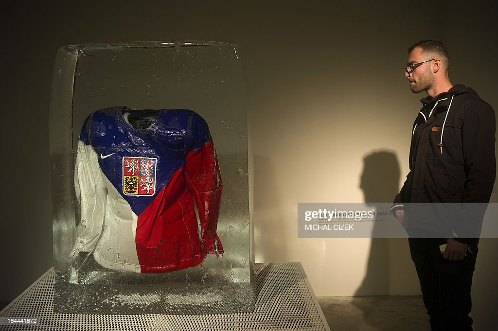 A visitor looks at an ice hockey jersey of the Czech national team, designed for the 2014 Winter Olypmics and frozen into a large ice cube, at the contemporary design festival 'Designblok 2013' on October 12, 2013 in Prague. Designblok is an international show of contemporary furniture, industrial design, interior accessories, lights, fashion and jewelry. Czech designers and selected foreign brands present their works from October 7 to 13, 2013 in the Czech Republic's capital. AFP PHOTO / MICHAL CIZEK