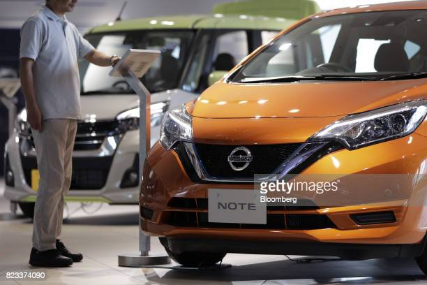 A visitor looks at an information panel for a Nissan Motor Co Note ePower hybrid vehicle at the company's showroom in Yokohama Japan on Thursday July...
