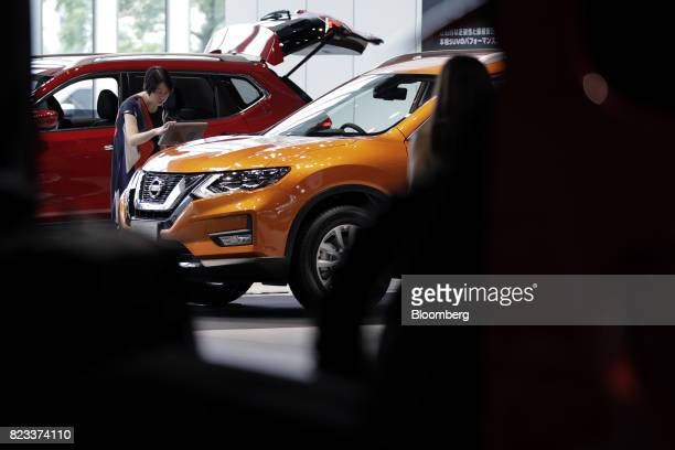 A visitor looks at an information panel for a Nissan Motor Co XTrail vehicle at the company's showroom in Yokohama Japan on Thursday July 27 2017...