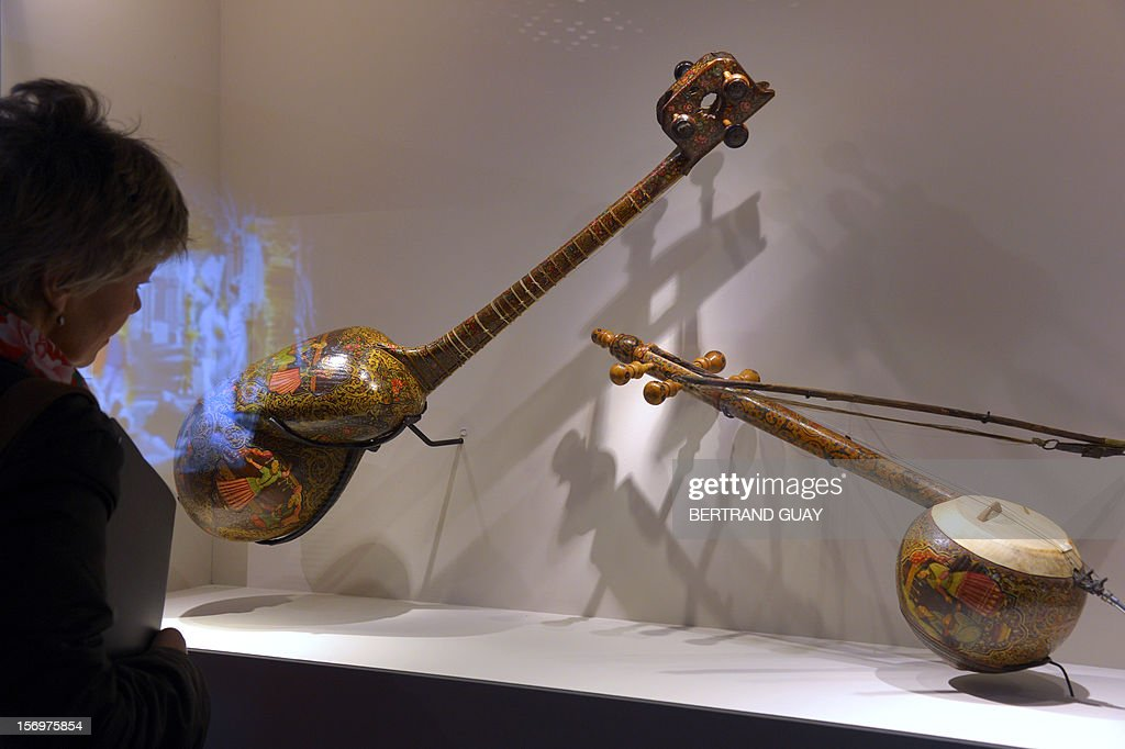 A visitor looks at an Iranian lute and an Iranian fiddle (R) displayed during the exhibition entitled 'Les Mille et une Nuits' (The thousand and one nights) at the Arab World Institute (IMA) on November 26, 2012 in Paris. The event runs until April 28, 2013.
