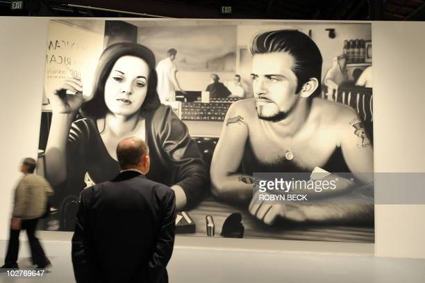 A visitor looks at an oil on vinyl painting called 'Biker Couple' at the press preview of 'Dennis Hopper Double Standard' the first US comprehensive...