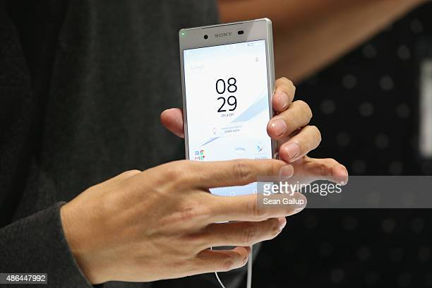 A visitor looks at an Xperia Z5 smartphone at the Sony stand at the 2015 IFA consumer electronics and appliances trade fair on September 4 2015 in...