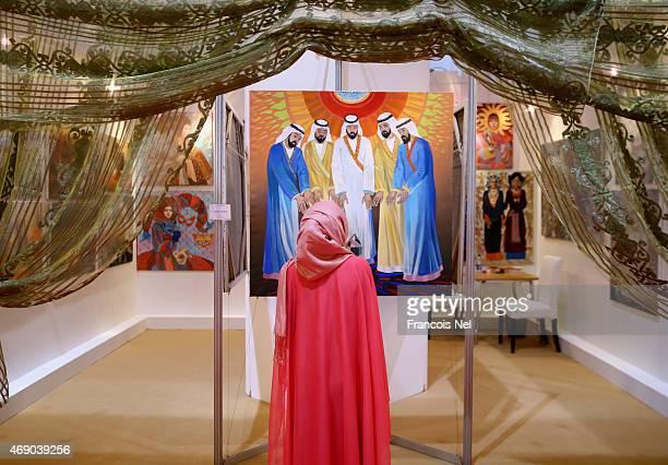 A visitor looks at artwork by artist Anatoly Silov during World Art Dubai 2015 at Dubai World Trade Centre on April 9 2015 in Dubai United Arab...