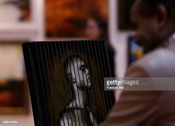 A visitor looks at artwork on display during World Art Dubai 2015 at Dubai World Trade Centre on April 9 2015 in Dubai United Arab Emirates