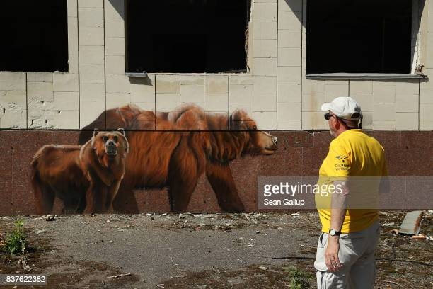 A visitor looks at bears painted by a graffiti artist that adorn the facade of an abandoned cultural center in the ghost town of Pripyat not far from...