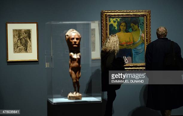 A visitor looks at creations by artist Paul Gauguin during a preview of the 'Gauguin Metamorphoses' exhibition at The Museum of Modern Art in New...