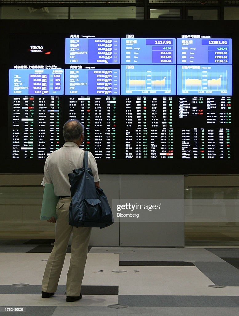 A visitor looks at electronic boards displaying stock figures at the Tokyo Stock Exchange in Tokyo Japan on Wednesday Aug 28 2013 Japanese shares...