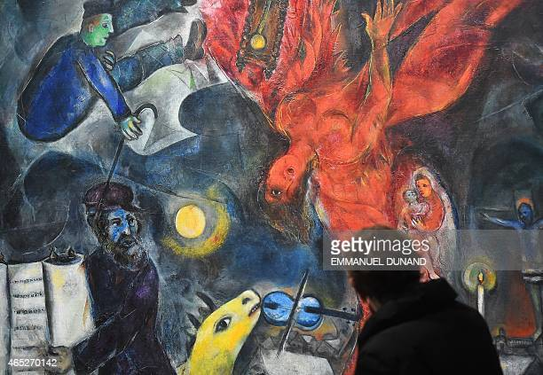 A visitor looks at FrenchRussian artist Marc Chagall's paintings during the 'Chagall Retrospective' exhibition at the Royal Museum of Fine Arts of...