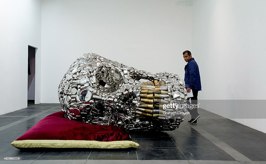 A visitor looks at Indian artist Subodh Gupta's sculpture ' Mind Shut Down' that is part of Gupta's first major museum show in New Delhi, 'Everything Is Inside' at National Gallery of Modern Art on January 16, 2014 in New Delhi, India.. The exhibition traces Gupta's career from his upbringing in the rural province of Bihar to his rise to prominence as one of India's foremost contemporary artists.The show draws together his varied body of work including painting sculpture, video and