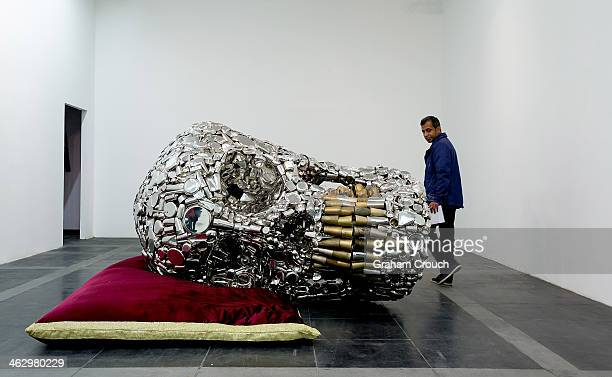 A visitor looks at Indian artist Subodh Gupta's sculpture ' Mind Shut Down' that is part of Gupta's first major museum show in New Delhi 'Everything...