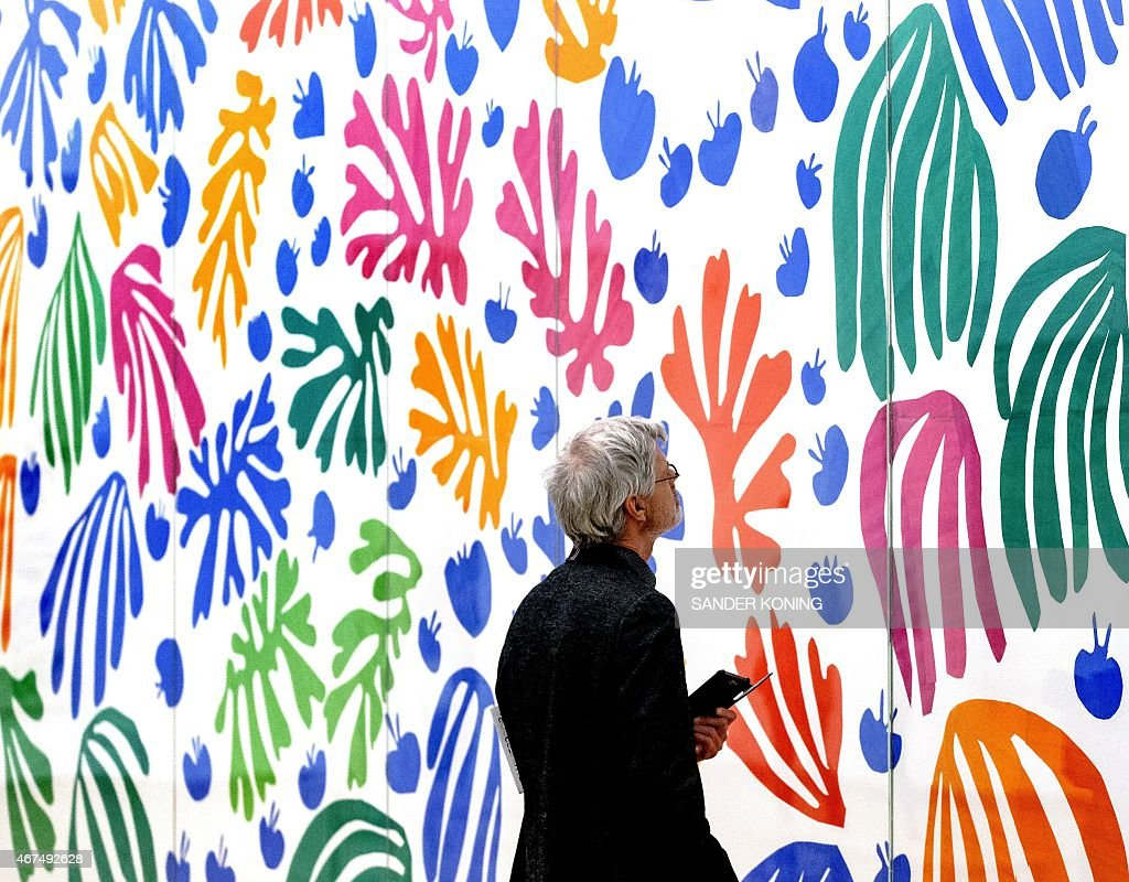 A visitor looks at La Perruche et la Sirene by French artist Henry Matisse at the previewing of the exhibition 'De Oase van Matisse' at the Stedelijk Museum, in Amsterdam, on March 25, 2015. The exhibit runs from March 27, to August 16, 2015. AFP PHOTO / ANP / SANDER KONING =NETHERLANDS OUT= CAPTION =